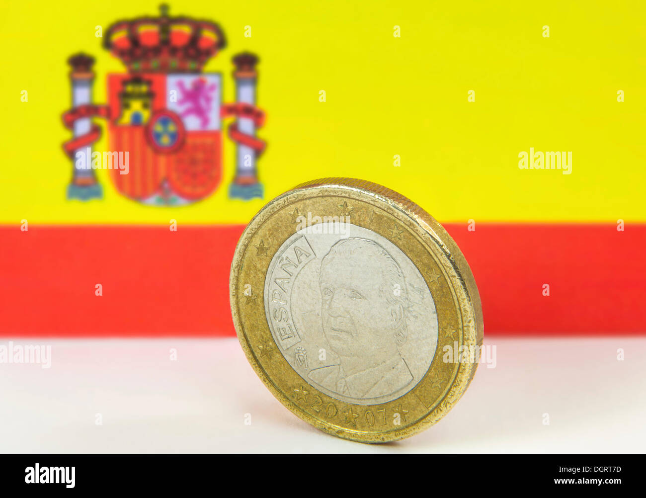 Old Spanish one euro coin in front of the Spanish flag - Stock Image