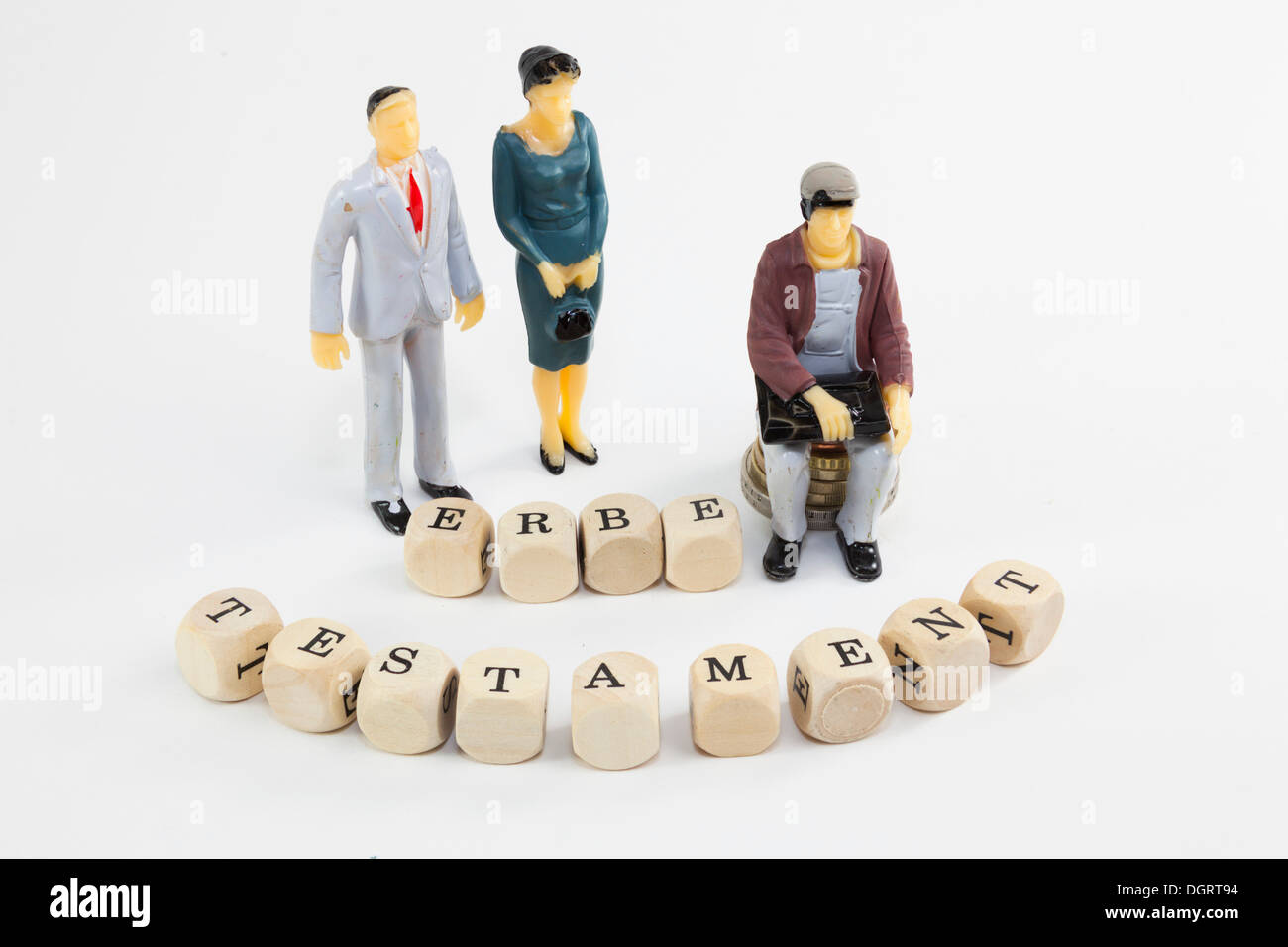 Miniature figures, letter cubes forming the word 'Erbe' and 'Testament', German for 'inheritance' and 'last will' - Stock Image