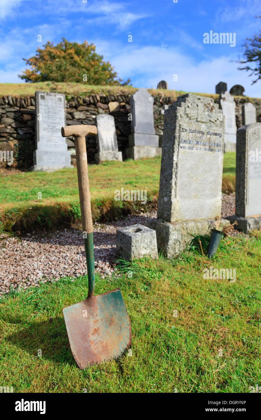 Shovel in graveyard - Stock Image
