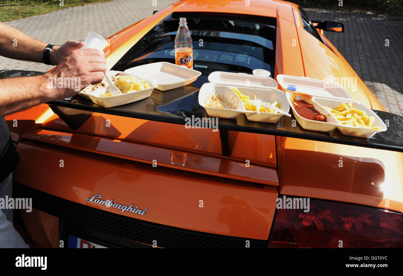 Rear wing of a IMSA Lamborghini Murcielago GTR, turned into a table for a meal with bratwurst and chips - Stock Image