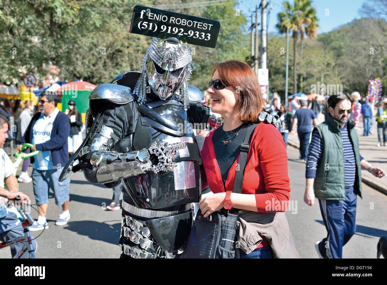 Brazil, Porto Alegre; Making fun with the Robot-Man at sunday open air market 'Brique da Redencao' - Stock Image