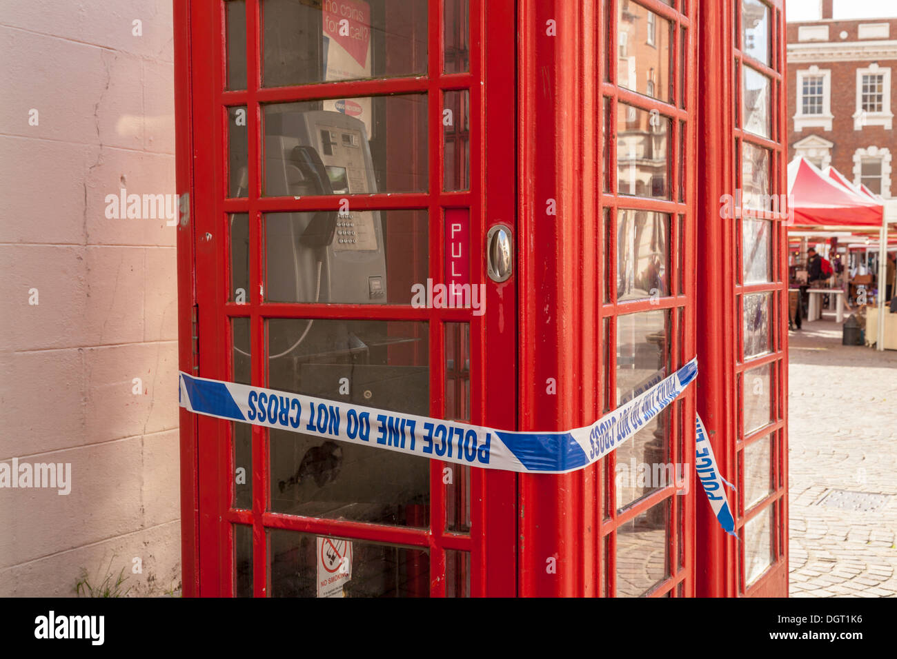 Police crime scene tape wrapped around a telephone kiosk, Newark on Trent, Nottinghamshire, England, UK - Stock Image