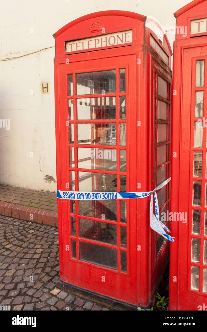 Police crime scene tape wrapped around a telephone box, Newark on Trent, Nottinghamshire, England, UK - Stock Image