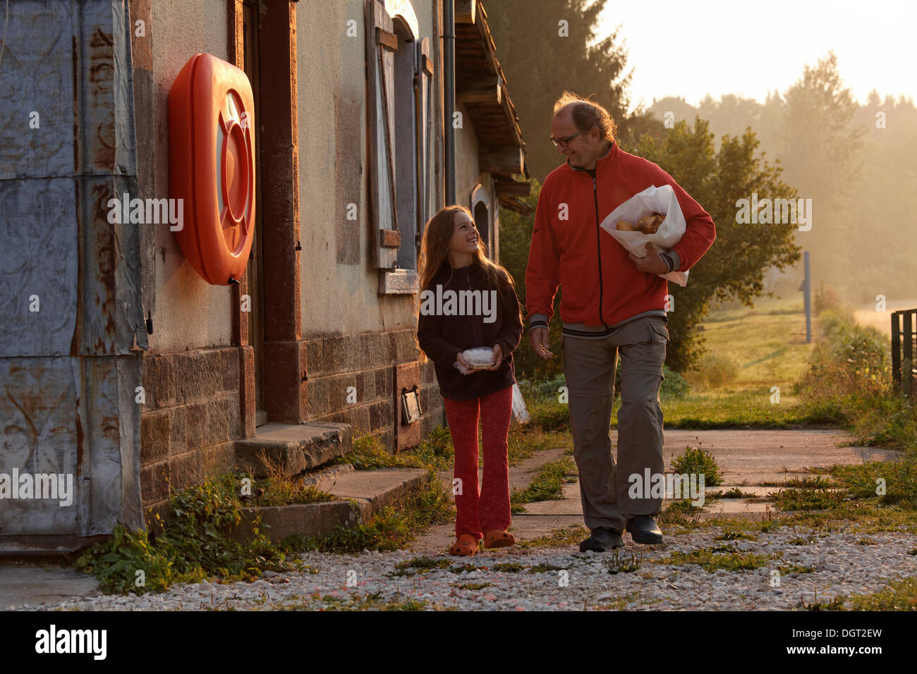 Father and daughter shopping for bread in the early morning, Selles, Vesoul, Region Franche-Comté, Dep. Haute-Saône, France - Stock Image