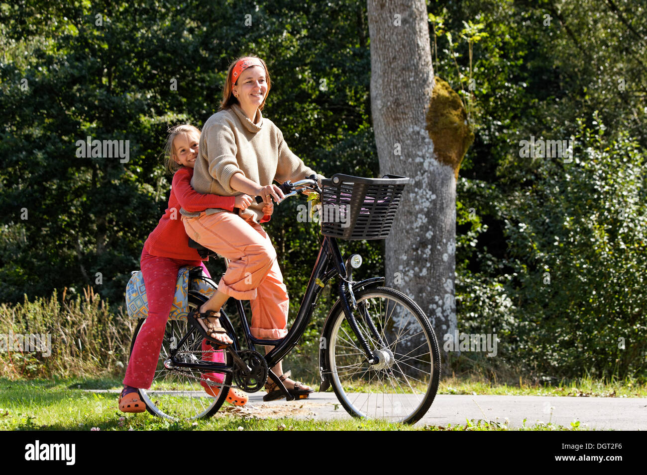 Mother and daughter riding a bicycle on the towpath alongside the Canal des Vosges, formerly Canal de l'Est, Uzemain, Epinal - Stock Image