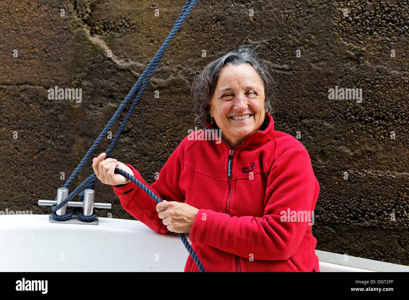 Holidaymaker holding a rope to secure the boat in the lock chamber, houseboat on the Canal des Vosges, formerly Canal de l'Est - Stock Image