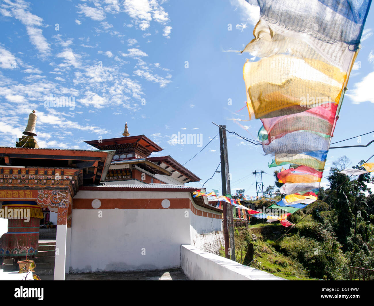 Small temple in Bhutan with colorful prayerflags during a sunny day - Stock Image