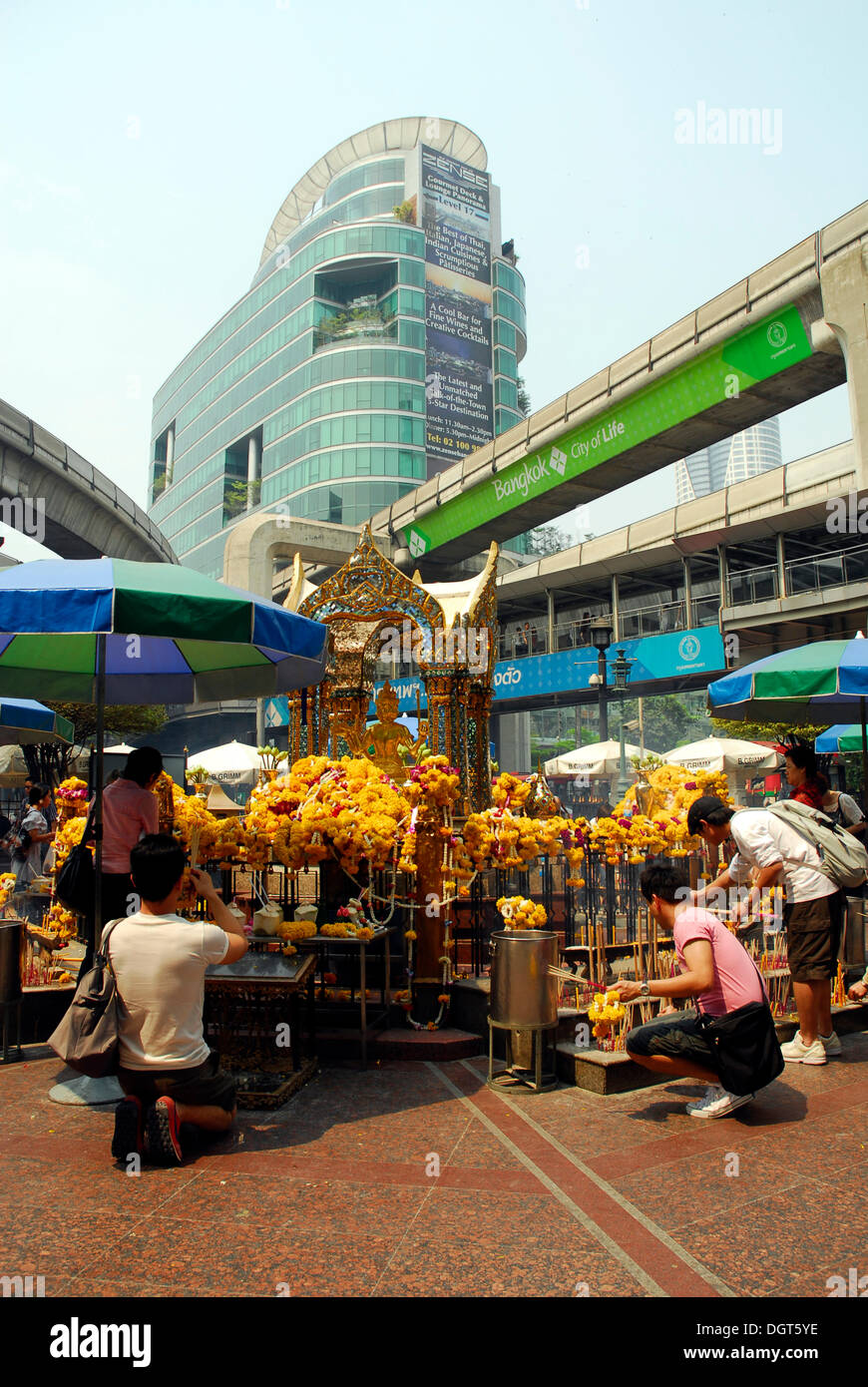 People worshipping at the altar, Erawan Shrine, Sky Train viaduct, Skytrain bridge at the junction Ploenchit and Stock Photo