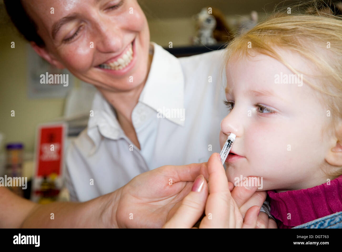 Three and a half year old child, accompanied by her mum / mother, receives a dose of the new flu vaccine - Fluenz - in the form of a nasal spray immunisation from her NHS GP Practice nurse. UK. - Stock Image
