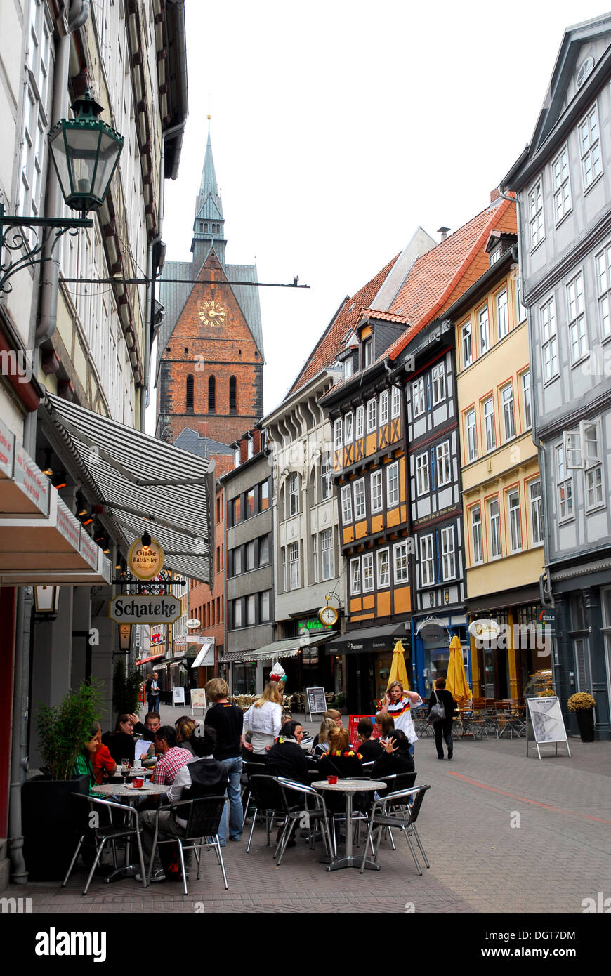 Cafe and bar in the old town, half-timbered houses in the Kramerstrasse street, in the back the Marktkirche church, Hannover - Stock Image
