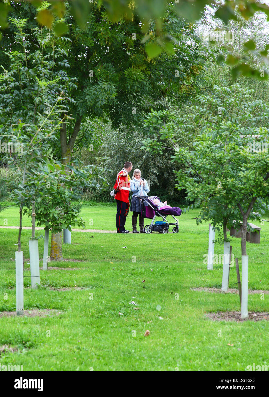 A soldier in dress uniform with his wife or partner and young child in a push chair at the National Memorial Arboretum, near Lichfield, Staffordshire, - Stock Image