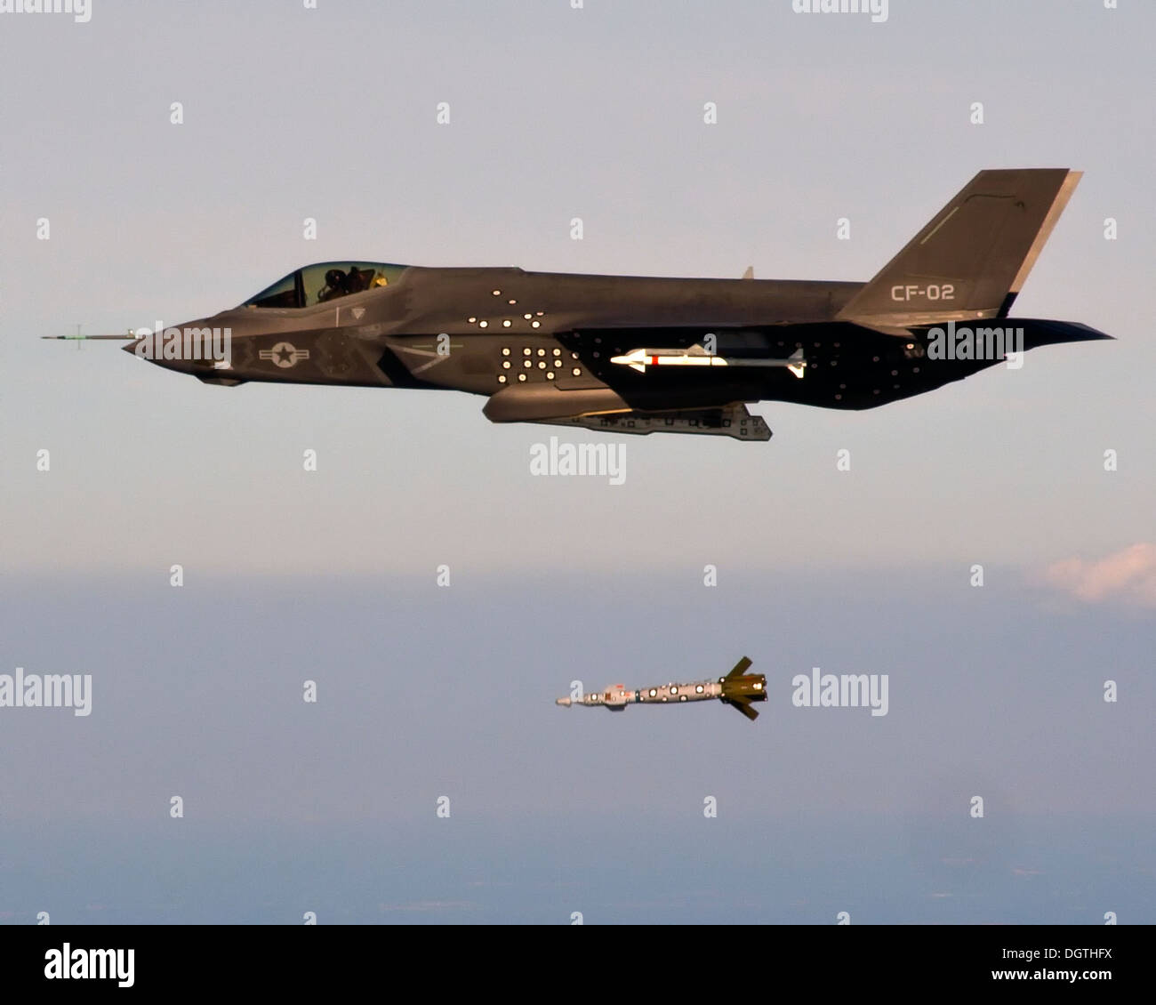 A US Marine Corps F-35C Lightning II Joint Strike Fighter stealth aircraft drops a 500-pound inert Guided Bomb Unit over the Atlantic test range October 22, 2013 Patuxent River, MD. - Stock Image