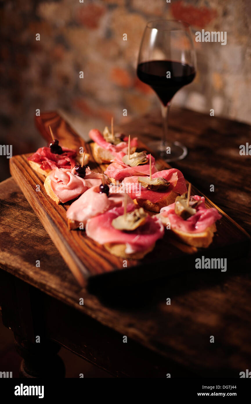Cured meats Cicchetti appetizers at La Mascareta Restaurant, Venice, Italy. - Stock Image