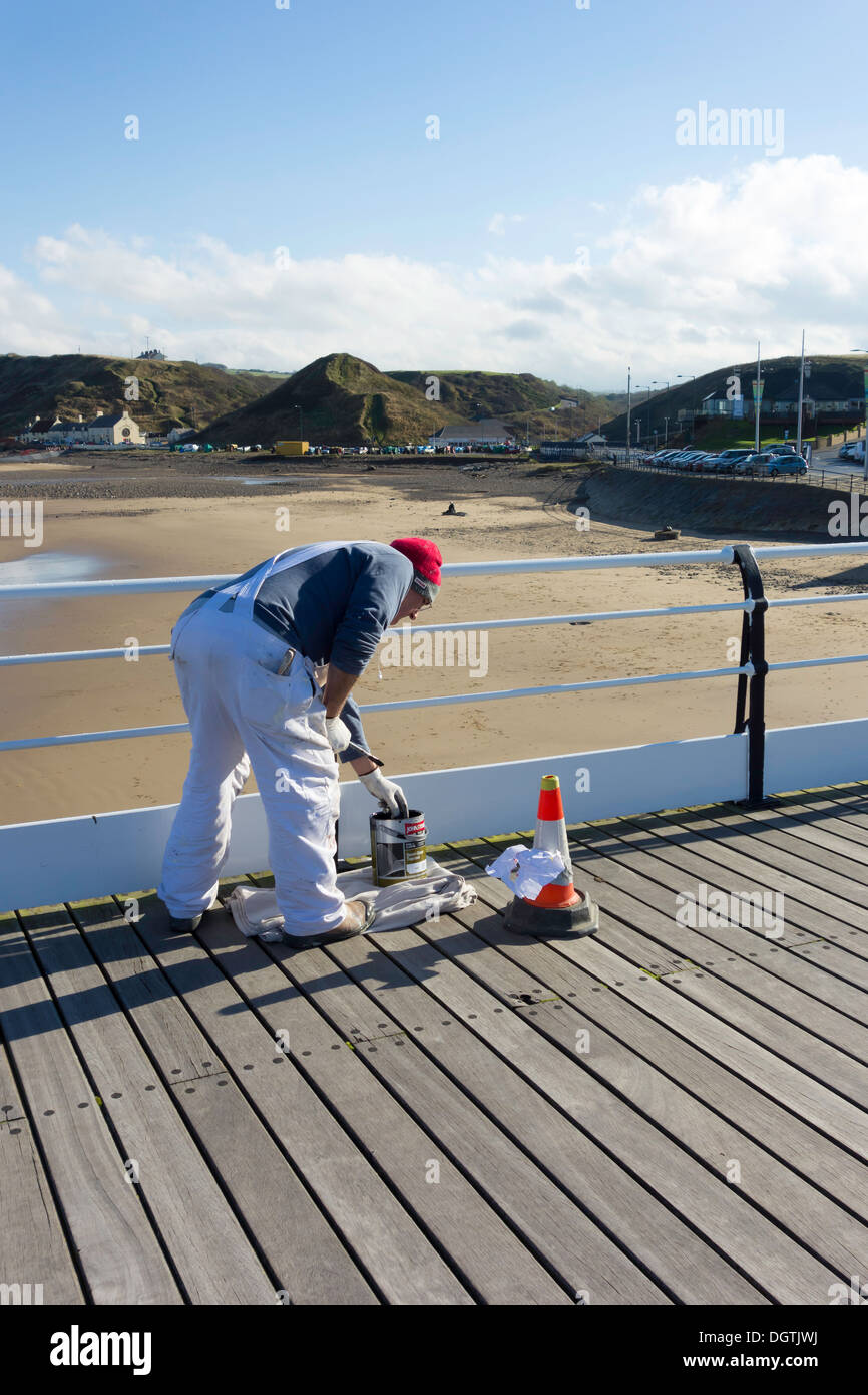 Painter at work repainting the hand rails on Saltburn Pier - Stock Image