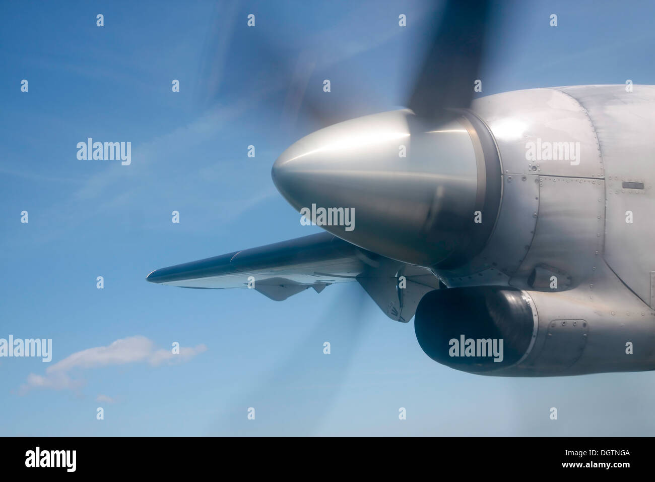Running silver propeller in front of blue sky - Stock Image