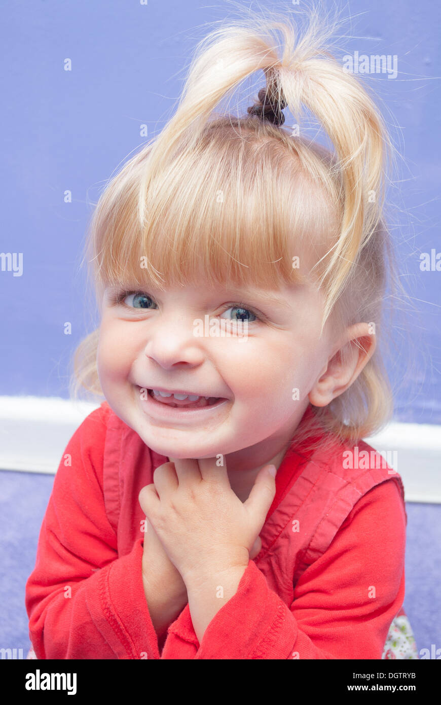 An eighteen Month old little girl smiling sweetly holding her hands under her chin. - Stock Image