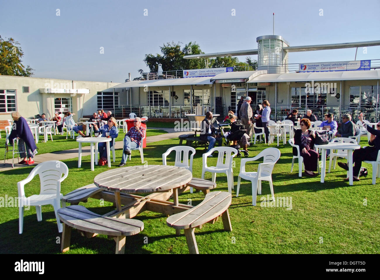 People socializing in the gardens of the Aviator Hotel at  Sywell Aerodrome Northamptonshire UK - Stock Image