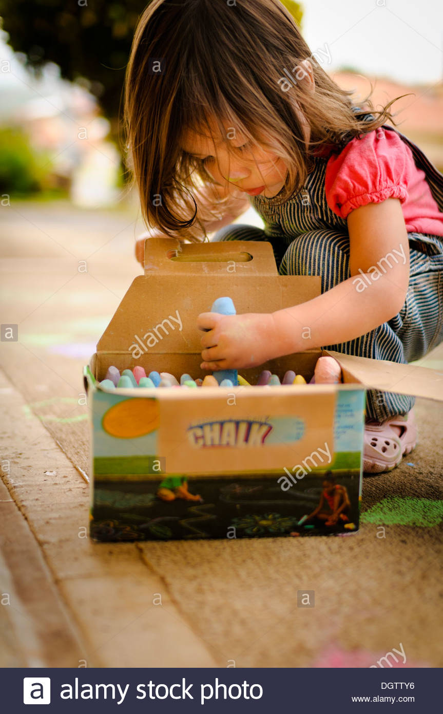 Toddler playing with chalk on the sidewalk. Stock Photo
