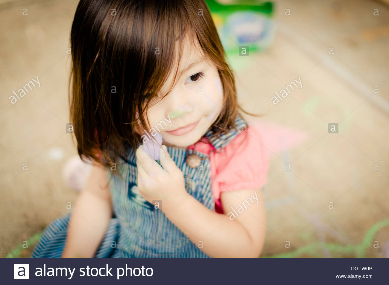 Toddler playing with chalk on the sidewalk. - Stock Image