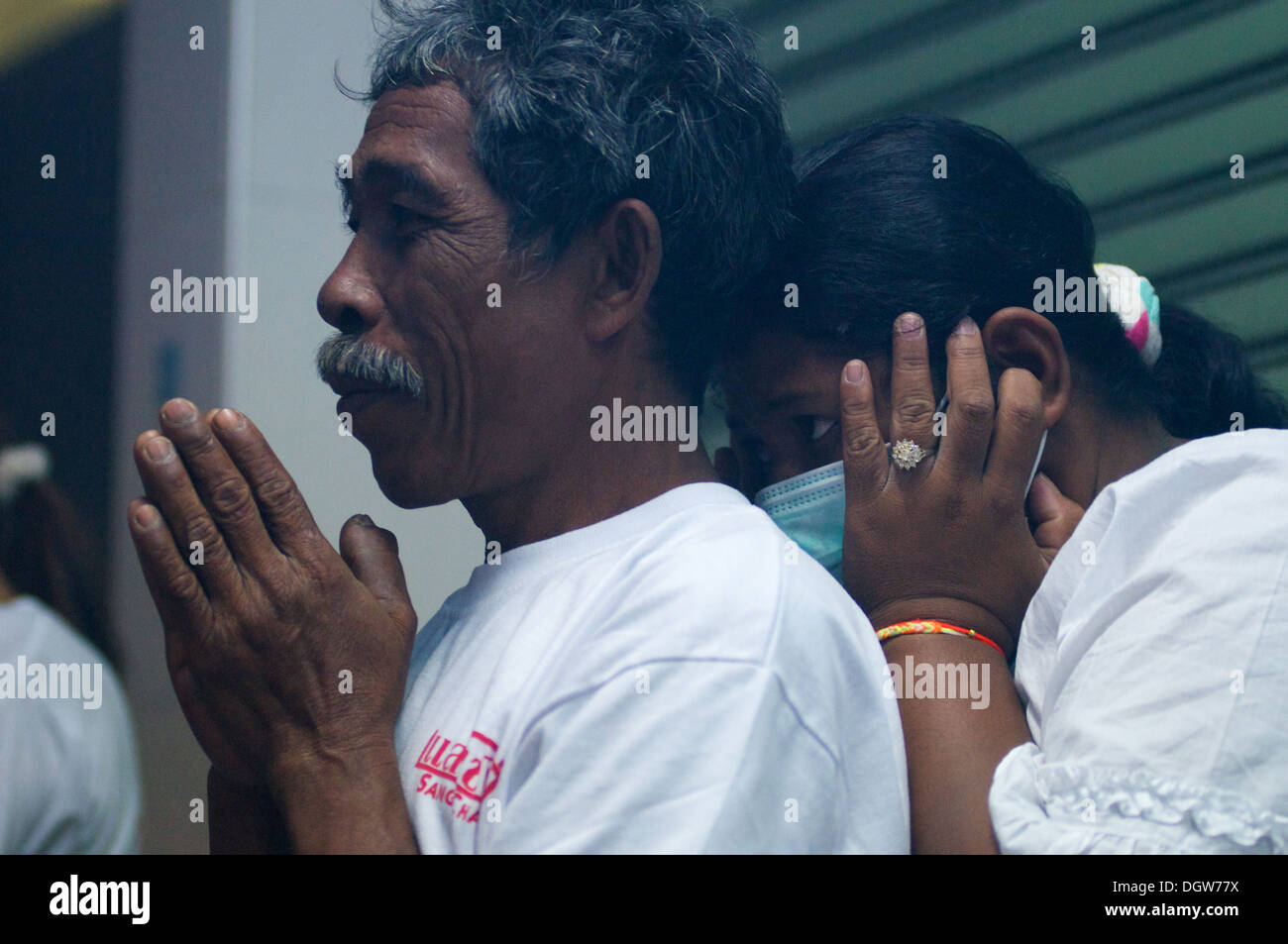 a Thai woman covers her ears & hides behind a man praying while firecrackers explode, the Vegetarian festival, Phuket, Thailand - Stock Image