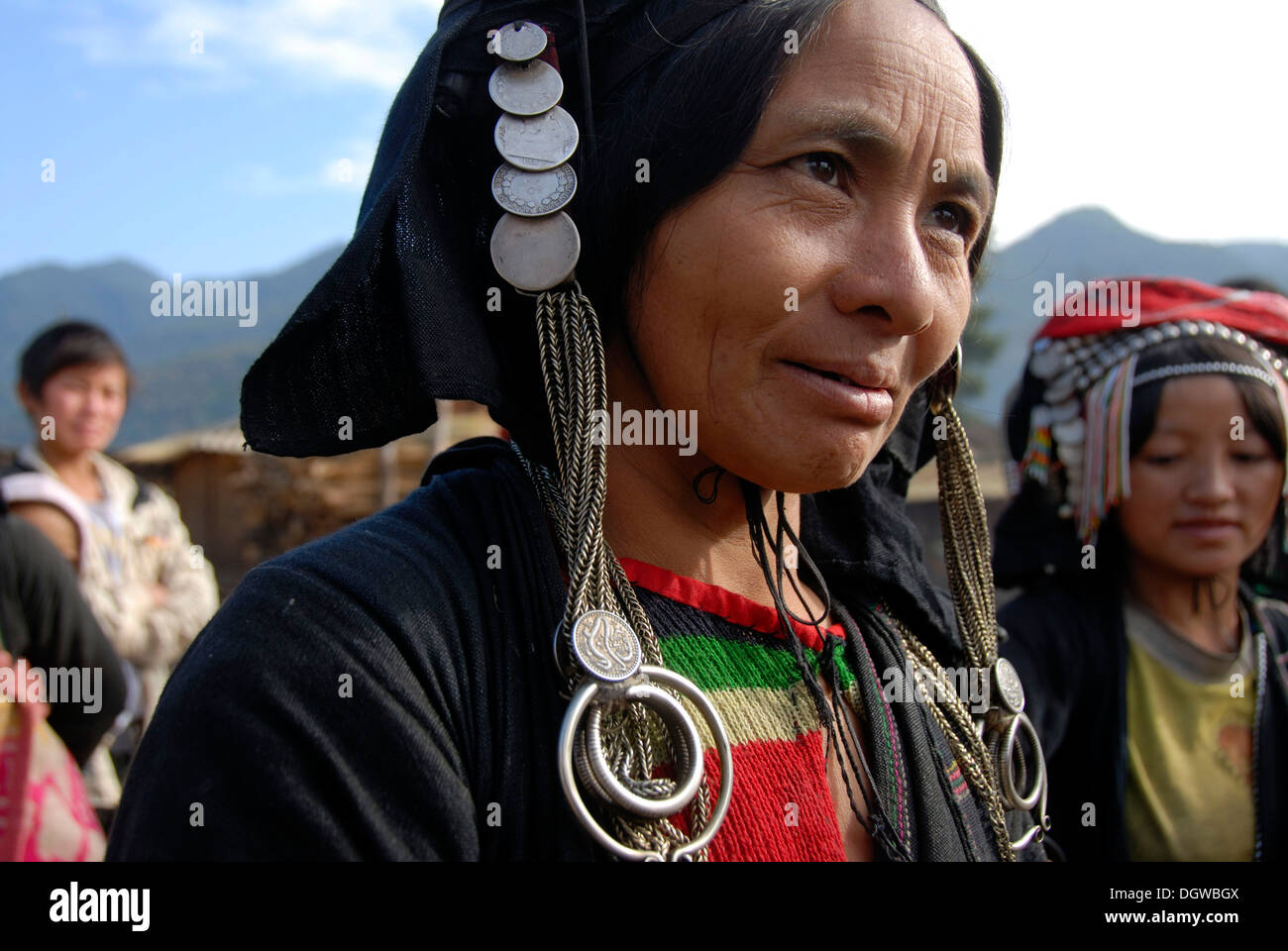 Portrait, smiling woman of the Phixor Akha ethnic group, traditional clothing dyed with indigo, headdress with silver Stock Photo