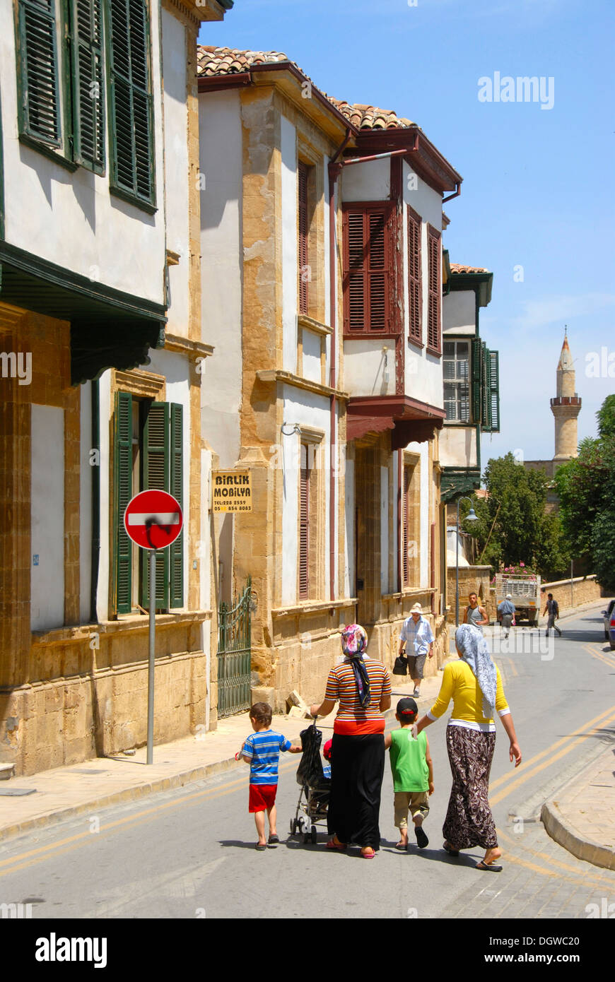 Historic Turkish architecture with bay windows, alleyway of the historic town centre with a minaret, Turkish family on the - Stock Image