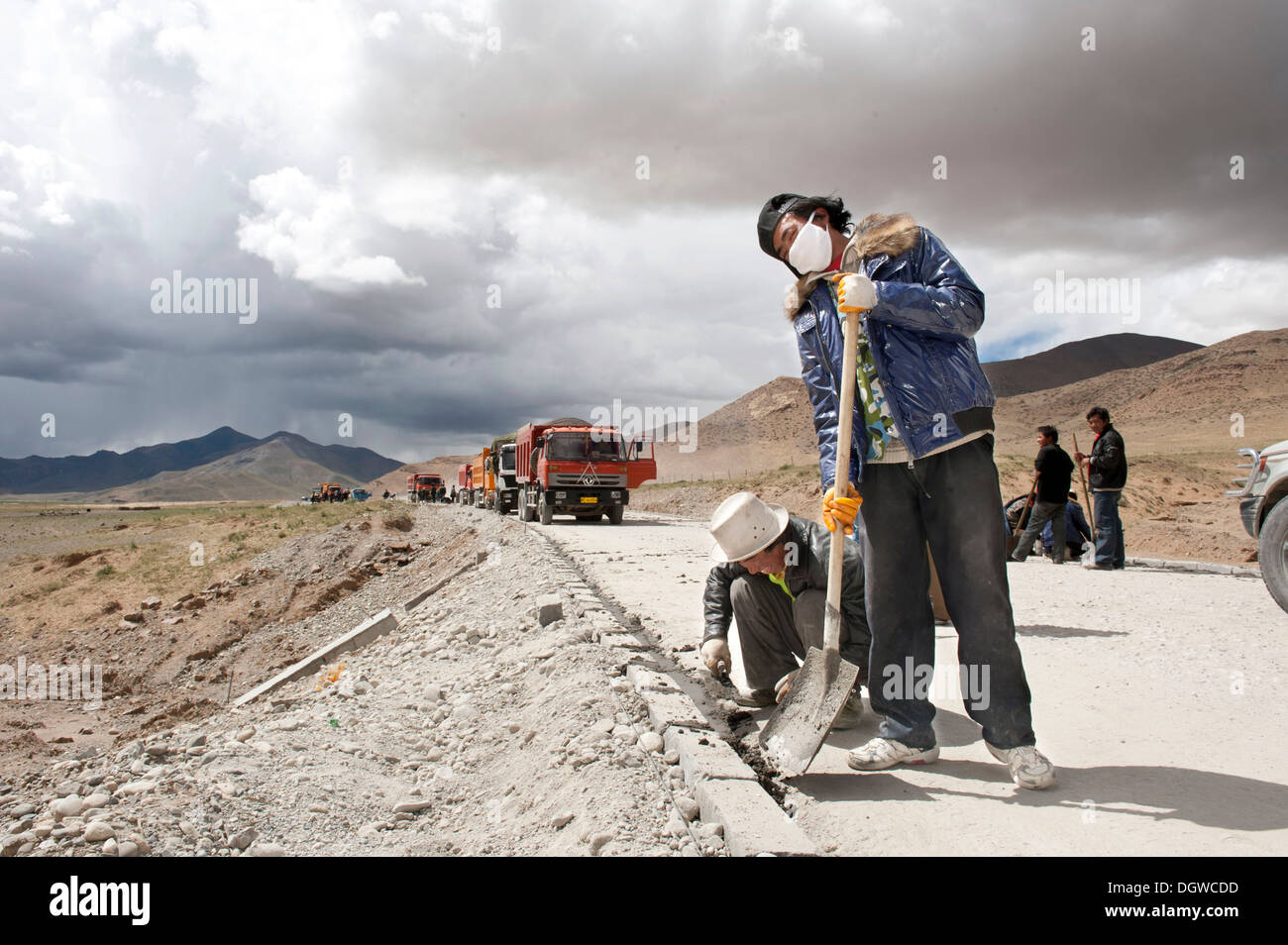 Road construction, Tibetan construction workers with shovels working on the G 219 road, China National Highway 219 - Stock Image