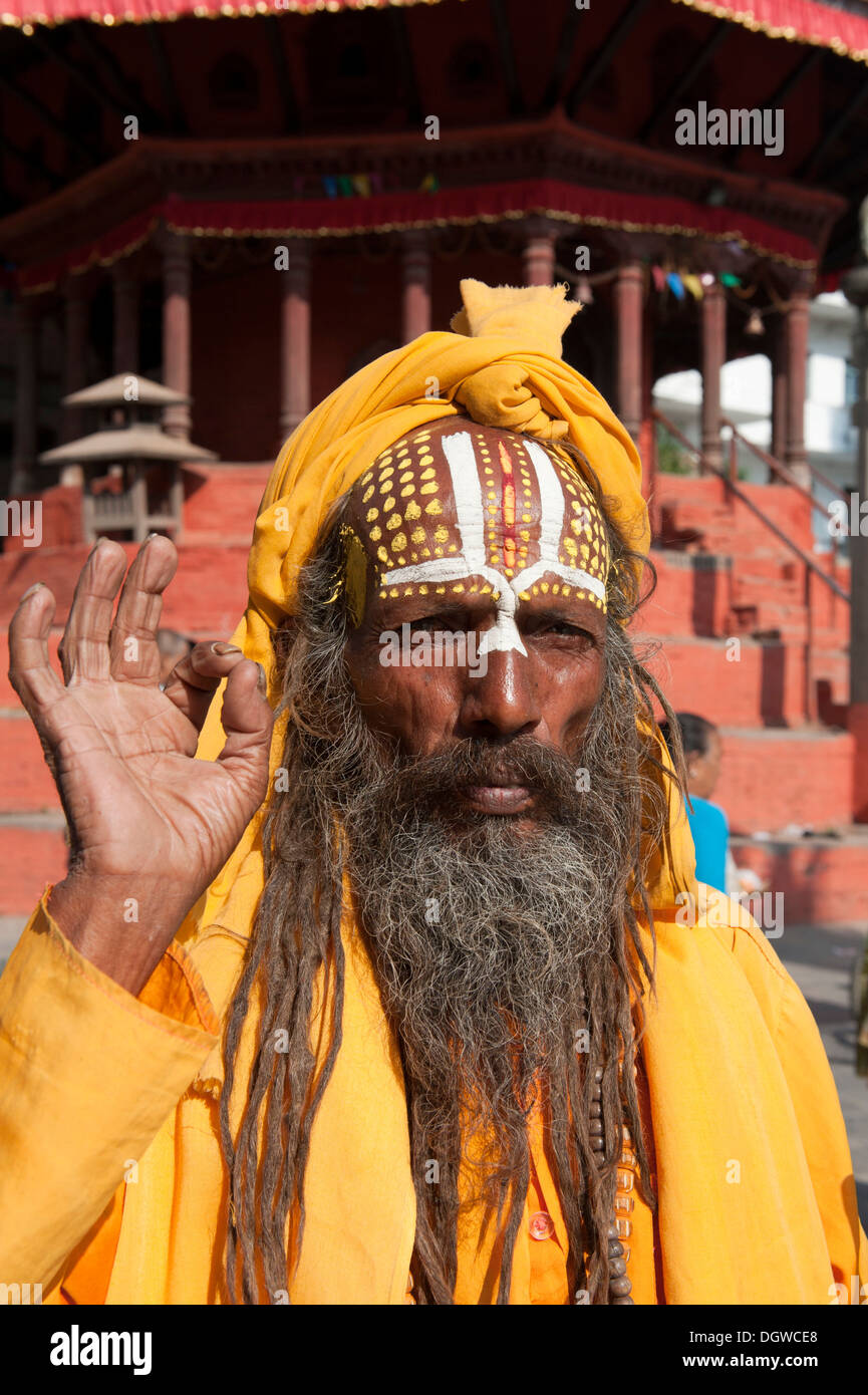 Portrait, holy man blessing with his hand, Mudra, Sadhu, brightly painted forehead, orange robe, beard, Hinduism, Stock Photo