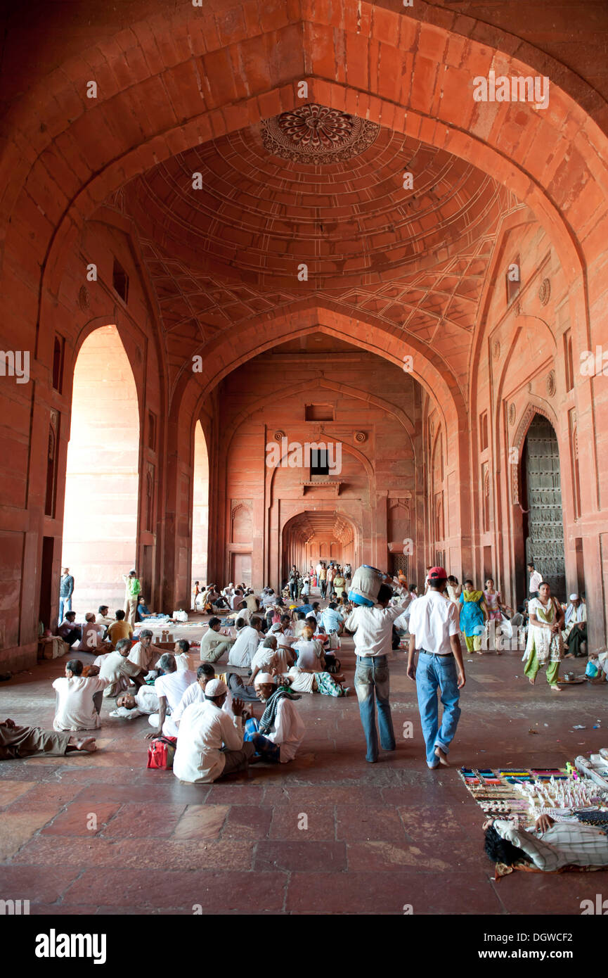 Mughal architecture, mosque, high ceiling, hall, believers, a lot of people sitting on the floor in the Buland Darwaza gate - Stock Image