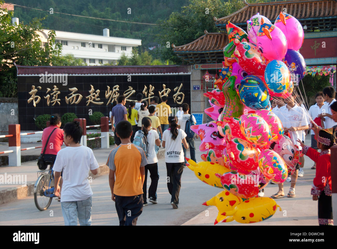 People walking along the street, kitsch, colourful balloons, Jiangcheng, Pu'er City, Yunnan Province, People's Republic of China - Stock Image