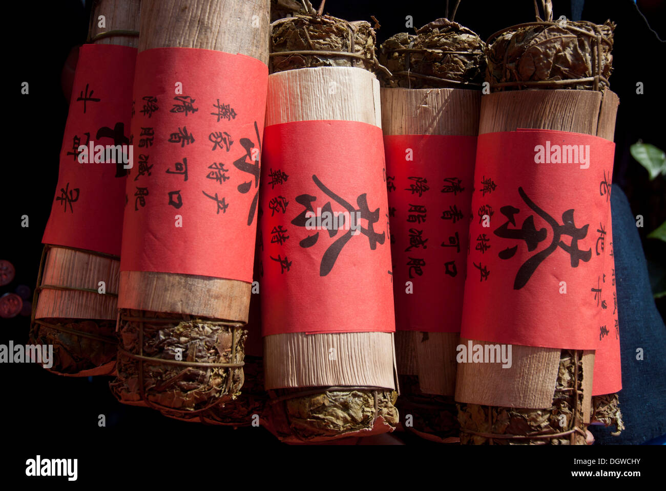 Green tea, compressed tea leaves wrapped in a red band with Chinese writing, Jiangcheng, Pu'er City, Yunnan Province - Stock Image