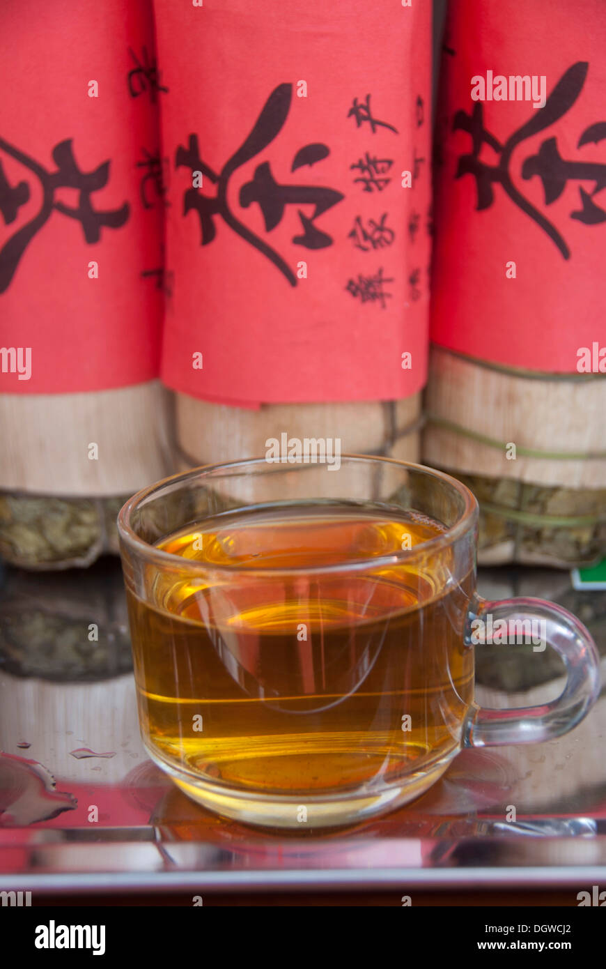 Green tea, tea cups, compressed tea leaves wrapped in a red band with Chinese writing, Jiangcheng, Pu'er City, Yunnan Province - Stock Image