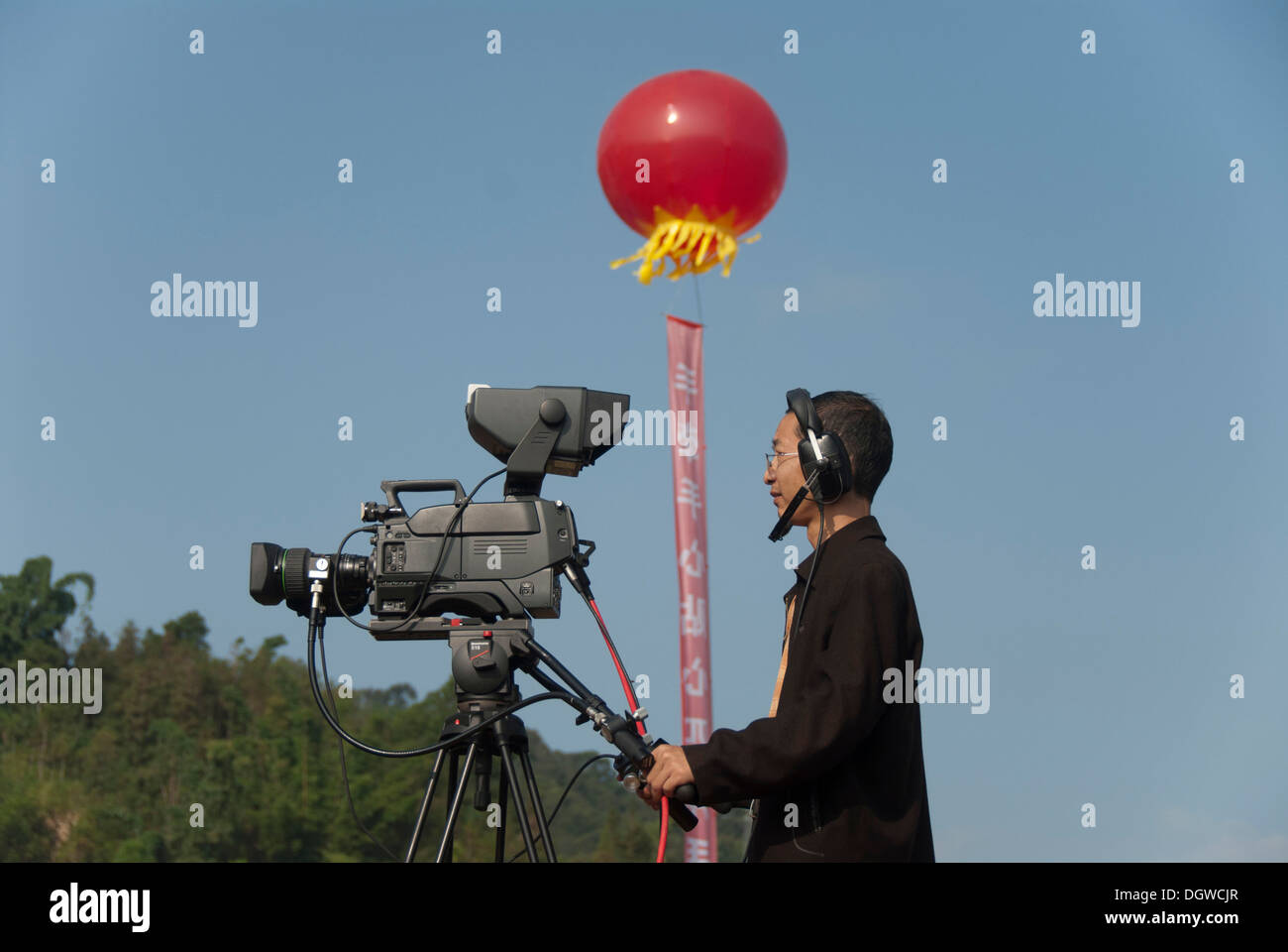 Cameraman with a television camera, TV broadcast of a festival, Jiangcheng, Pu'er City, Yunnan Province - Stock Image