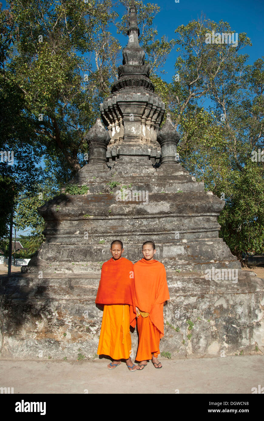 Two monks in orange robes in front of a stupa, novices, Vat Aham, Wat, Luang Prabang province, Laos, Southeast Asia, Asia - Stock Image