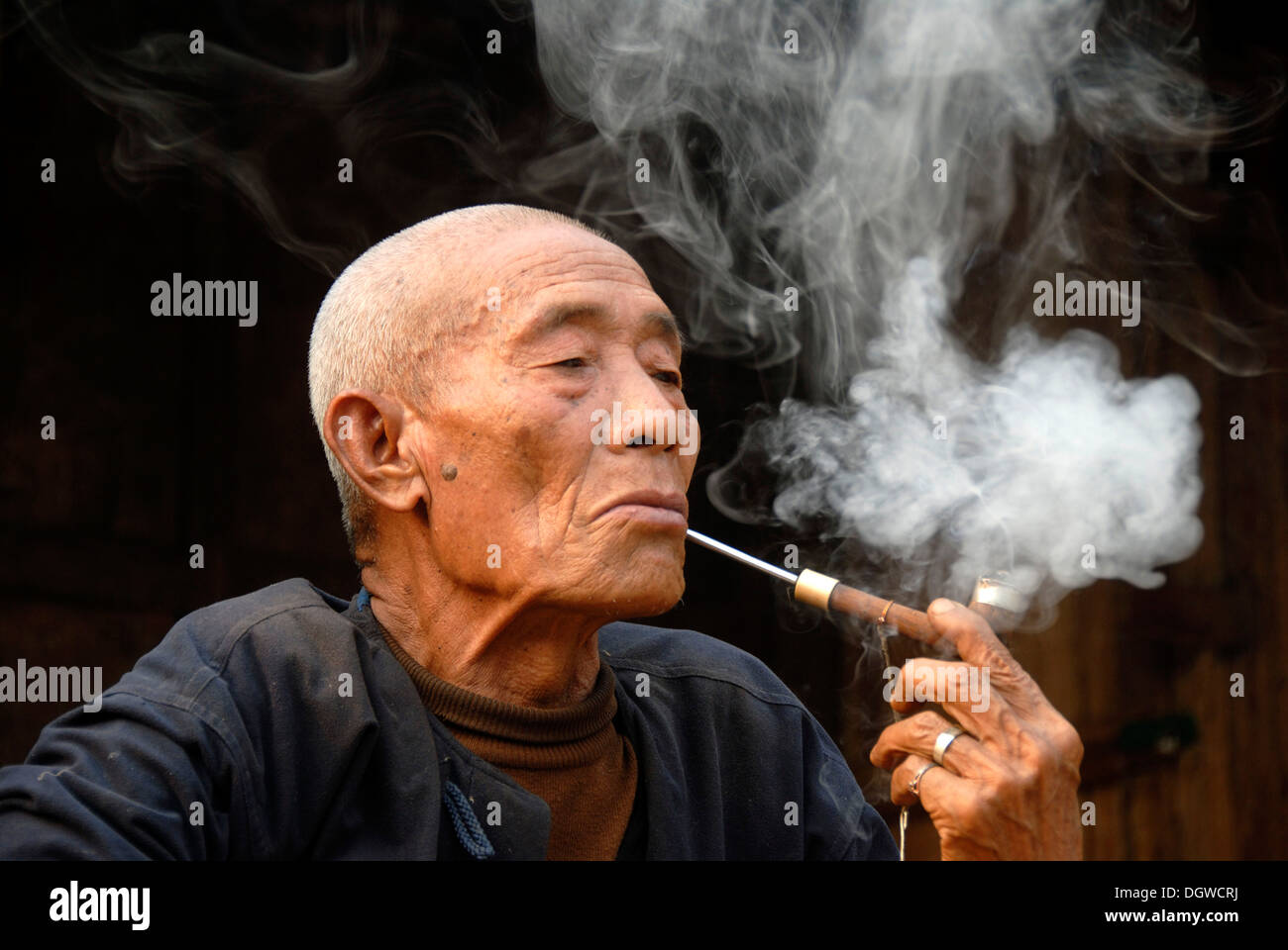 Male smoker, portrait, indulgence, old man of the Mouchi ethnic group smoking a pipe, smoke lingering in the air - Stock Image
