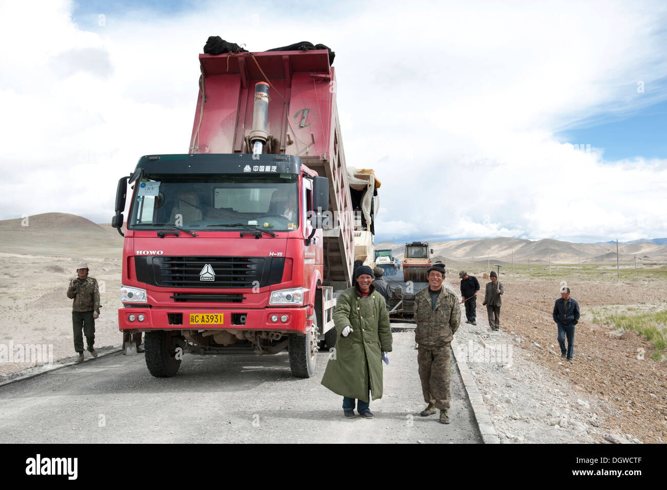Trucks at road constructions through the Tibetan highlands, Street G 219, supervisor in a coat, Trans-Himalaya, Himalayas - Stock Image