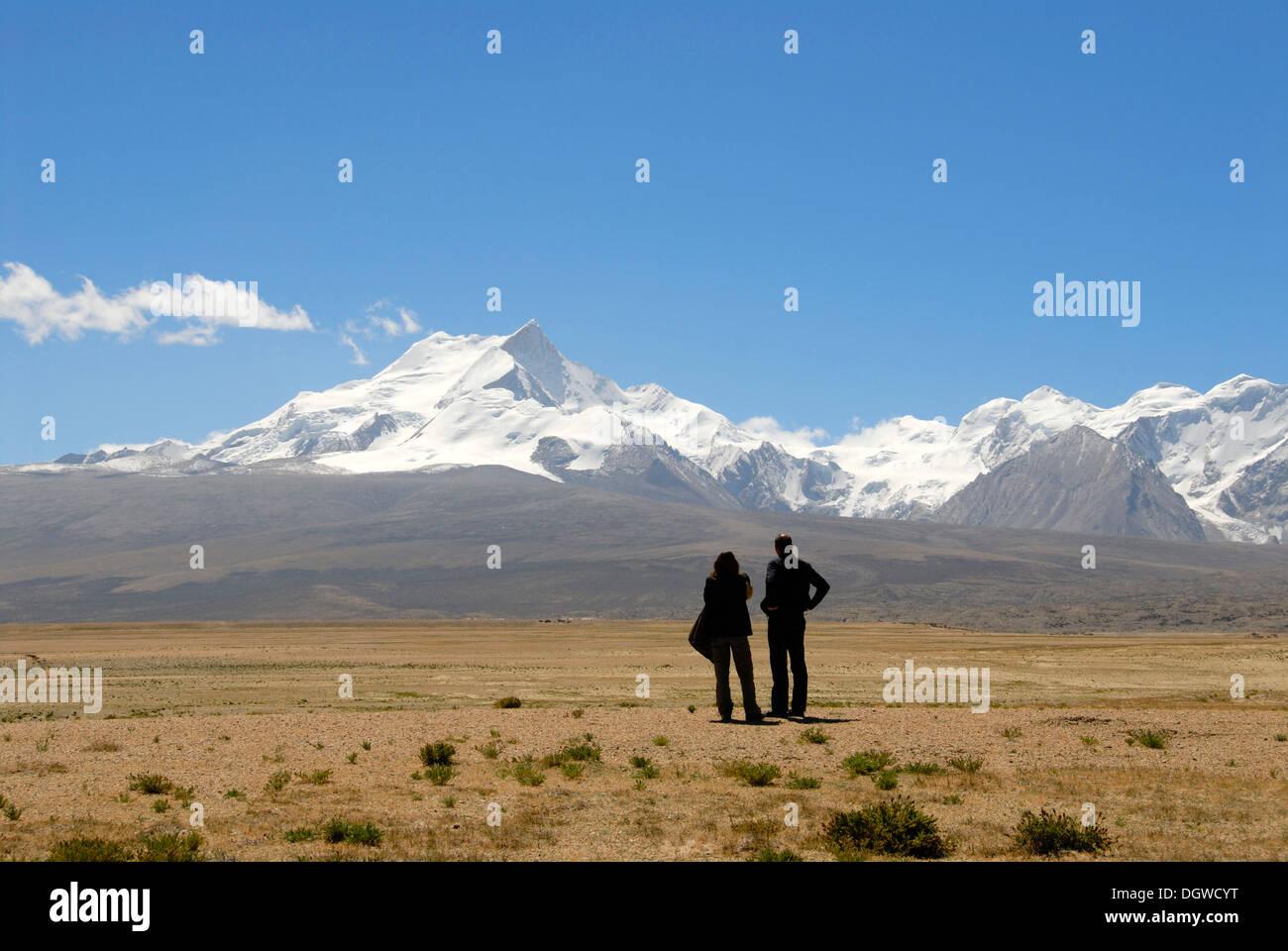 Two people in silhouette, wide landscape, near Lake Pelku Tso, high plateau, looking towards Mount Shishapangma, 8013 m - Stock Image