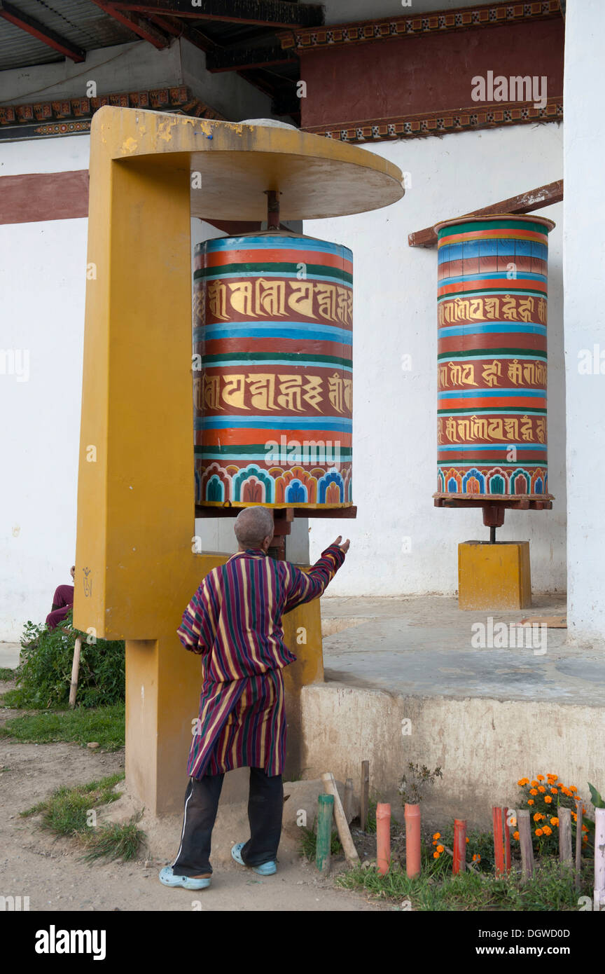 Tibetan Buddhism, believer spinning a large modern prayer wheel, Thimphu, the Himalayas, Kingdom of Bhutan, South Asia, Asia - Stock Image