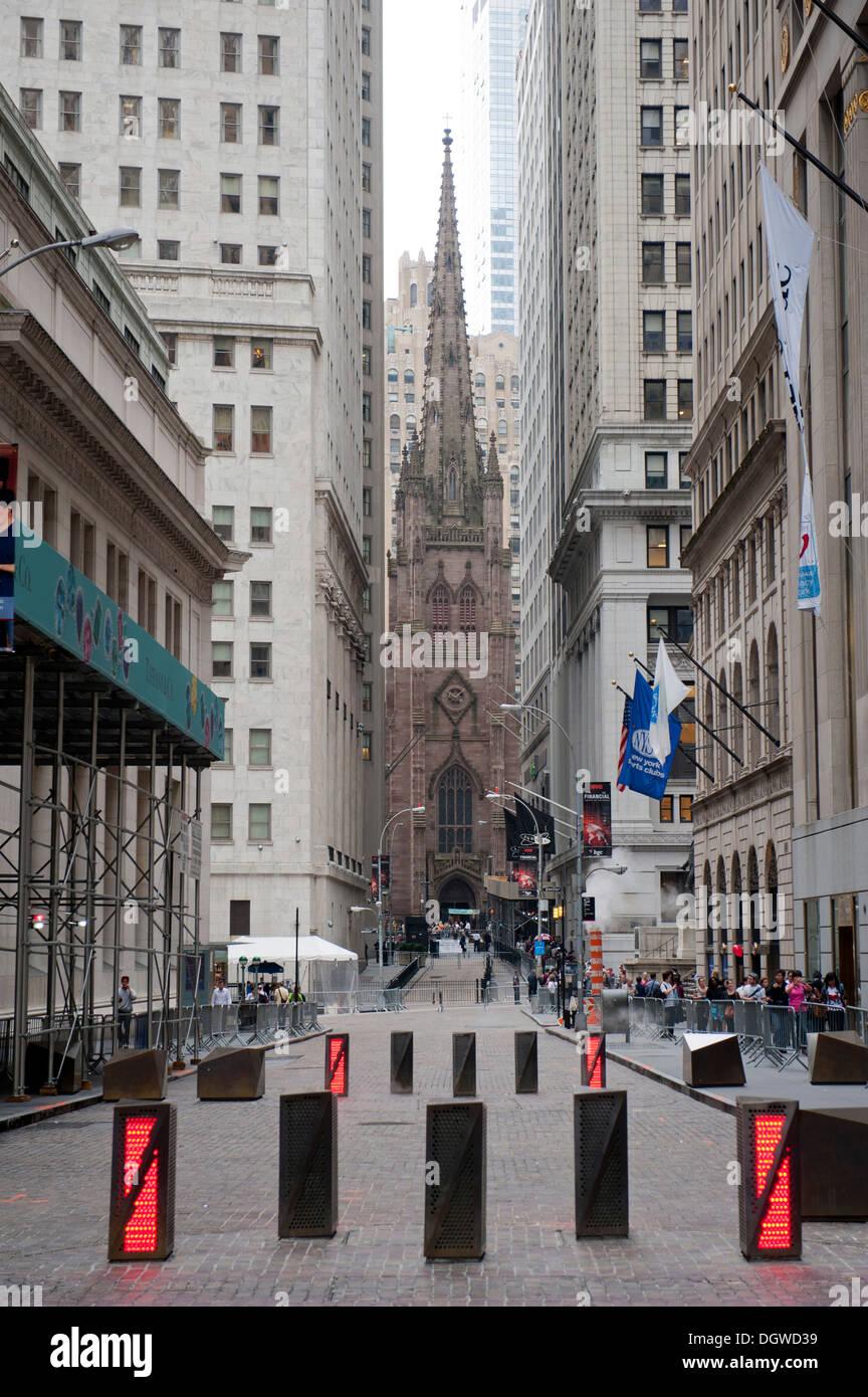Road block, view through the blocked Wall Street towards Trinity Church, Financial District, Lower Manhattan, New York City, USA - Stock Image