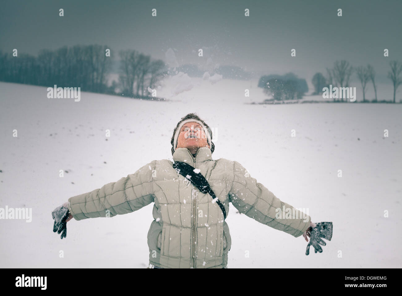 Ecstatic middle aged woman enjoying snow in winter. - Stock Image