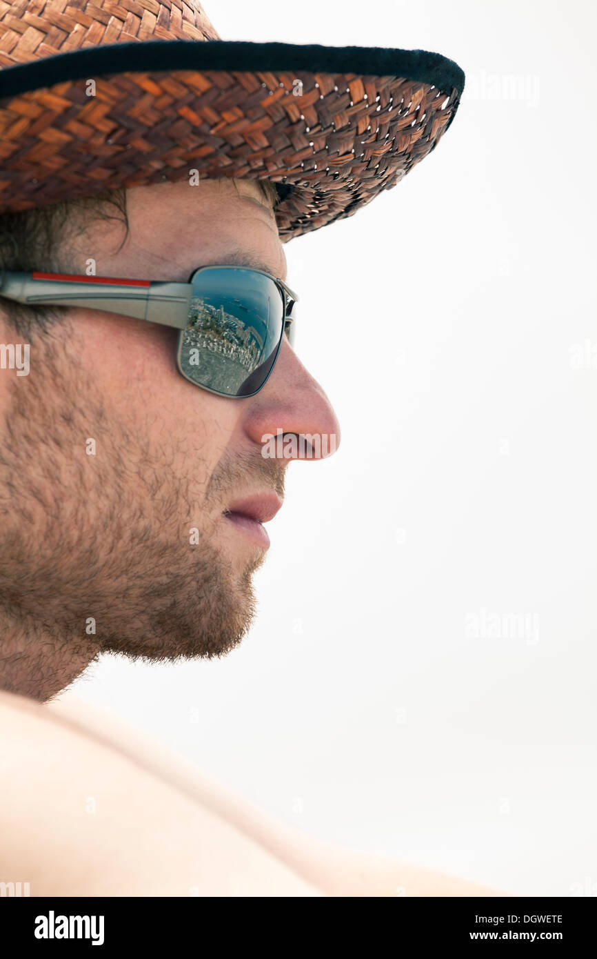Closeup of young unshaved man in hat and sunglasses. - Stock Image