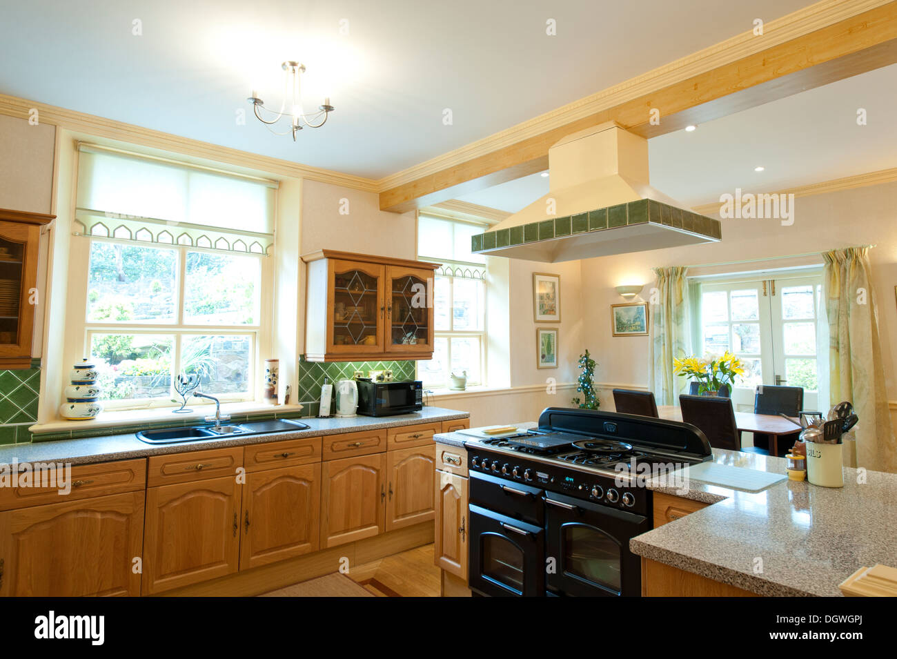 Large open plan modern kitchen central hob - Stock Image