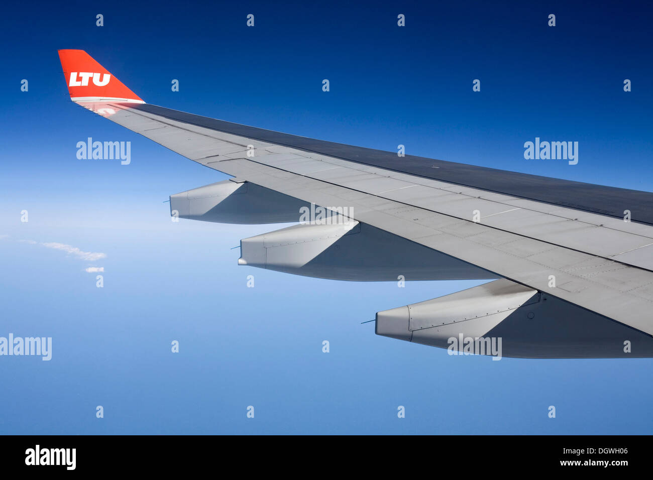 Wing of an Airbus aircraft in flight, with winglet and the logo of airline LTU, over the Atlantic Ocean - Stock Image