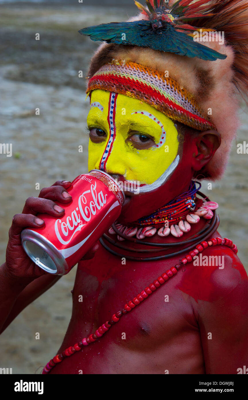 Colourfully decorated and painted boy drinking from a Coke can during the traditional Sing Sing in the highlands, Enga - Stock Image