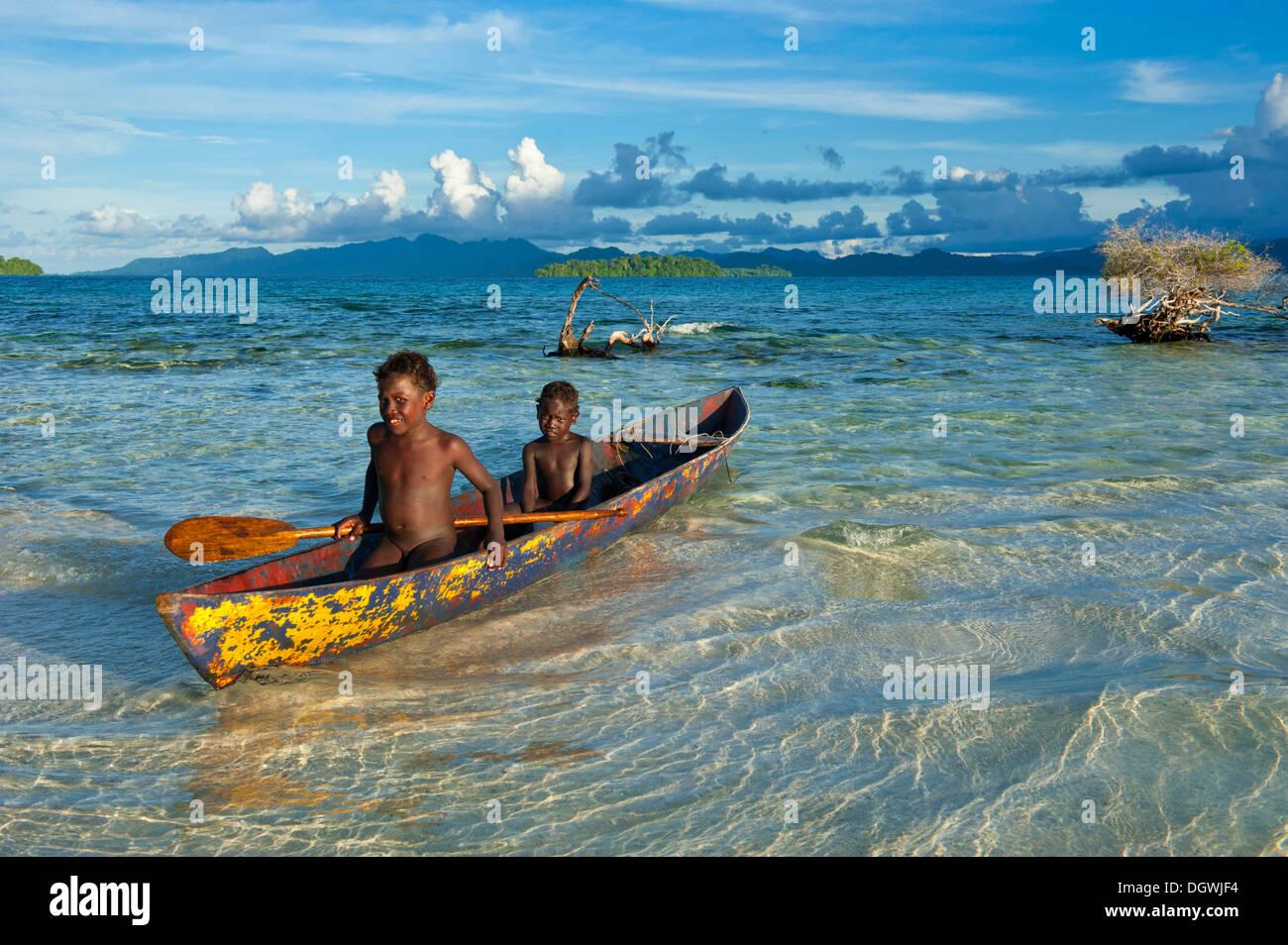 Boys in a canoe in the Marovo Lagoon, Marovo Lagoon, Western Province, Solomon Islands - Stock Image