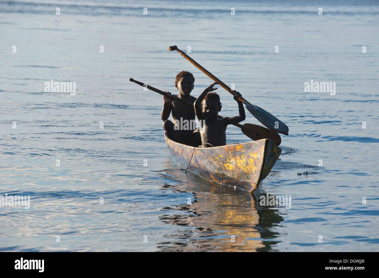 Boys in a canoe in backlight, Marovo Lagoon, Western Province, Solomon Islands - Stock Image