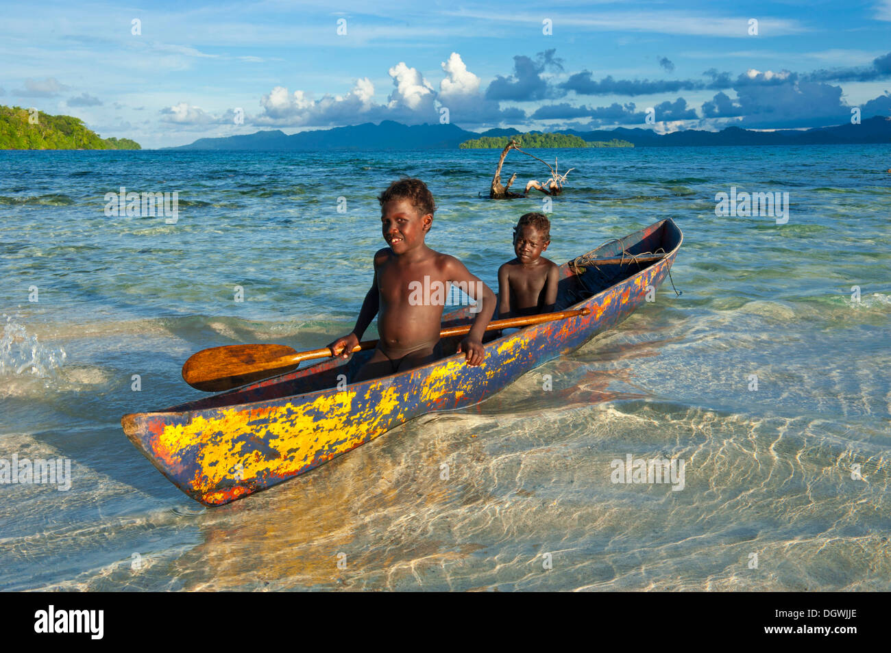 Boys in a canoe in the Marovo Lagoon, Marovo Lagoon, Western Province, Solomon Islands - Stock Image