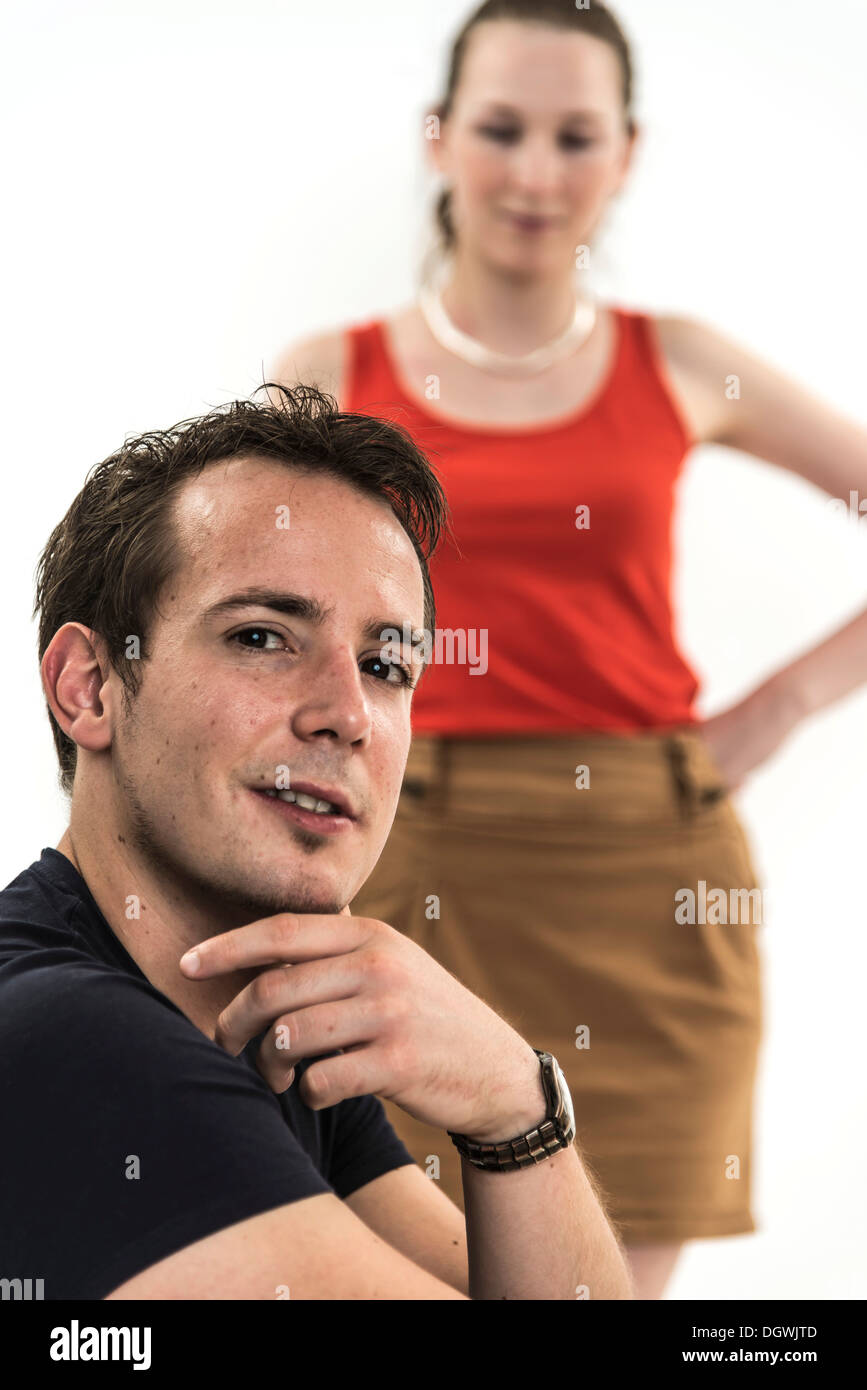 Man thinking, out of focus behind him stands a beautiful woman, symbolic image for temptation - Stock Image