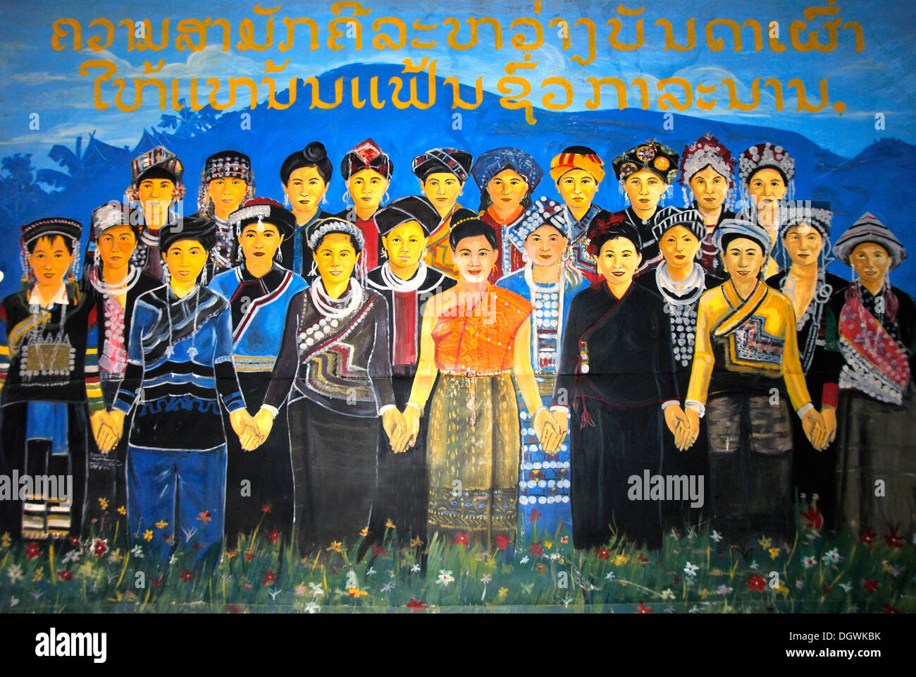 Painted communist propaganda poster, with lettering in Laotian script, advertising the friendship between the ethnic groups, - Stock Image