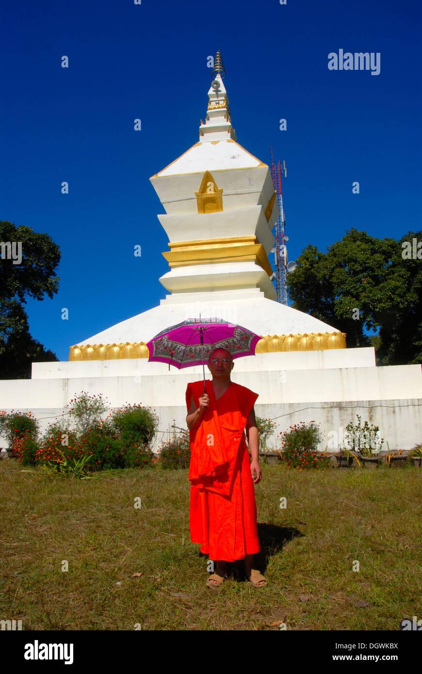 Monk with parasol, orange robe, white stupa, Phu Fa mountain, Phongsali, Laos, Southeast Asia, Asia - Stock Image
